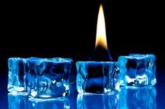 Fiamma che brucia sui cubi di ghiaccio blu Fotografia Stock