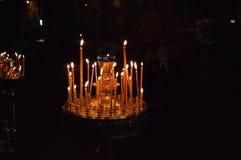 Fiamma delle candele della cera nella chiesa immagine stock