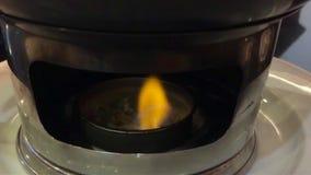 Fiamma di alcool solido che brucia sotto il vaso dell'alimento dell'acciaio inossidabile al ristorante video d archivio