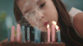 Fiamma di candela di salto della ragazza graziosa sulla torta di compleanno al rallentatore Buon compleanno stock footage