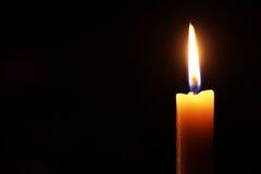 Fiamma di candela sul nero immagini stock libere da diritti