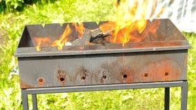 Fiamma luminosa quando legno bruciante in camino del metallo all'aperto, fuoco e carboni caldi per il barbecue, fuoco giallo dell archivi video