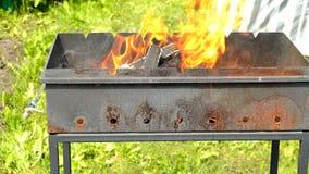 Fiamma luminosa quando legno bruciante in camino del metallo all'aperto, fuoco e carboni caldi per il barbecue, fuoco giallo dell video d archivio