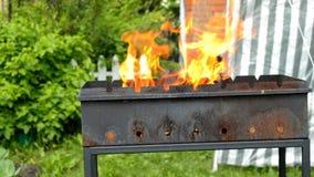 Fiamma luminosa quando legno bruciante in camino del metallo all'aperto, fuoco e carboni caldi per il barbecue, fuoco giallo dell stock footage