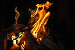 Fiamme arancio del fuoco nel camino scuro Casa accogliente e calda immagine stock libera da diritti
