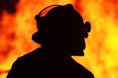 Fiamme del fuoco della parte anteriore dell'ufficiale del vigile del fuoco della siluetta una Fotografia Stock