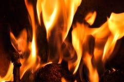 Fiamme del fuoco su una priorità bassa nera Parte posteriore di struttura della fiamma del fuoco della fiammata Fotografia Stock