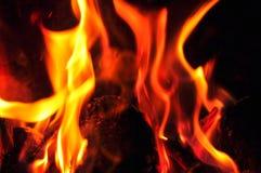 Fiamme del fuoco su una priorità bassa nera Parte posteriore di struttura della fiamma del fuoco della fiammata Fotografie Stock