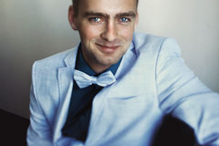 Fiance with blue eyes wearing blue suit with bow tie Royalty Free Stock Image