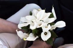 Fiance die een huwelijksboeket van callas bloemen houden royalty-vrije stock afbeeldingen