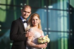 Fiance and fiancee near futuristic building. Tender fiance and fiancee on their wedding day standing near futuristic modern building with big windows. fiance is royalty free stock photos