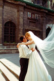 Fiance holds bride's waist tenderly while she stands on footstep Stock Photos
