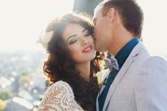 Fiance kisses a bride while wind is playing with her curly hair Royalty Free Stock Photography