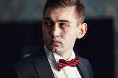 Fiance with red bow tie looks seriously Royalty Free Stock Photos