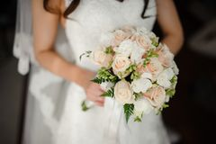 Fiancee in a beautiful white dress holding a bouquet. Fiancee in a beautiful white dress holding a beautiful bouquet of wedding flowers made of tender roses in Stock Image