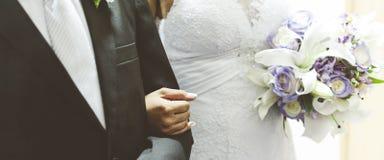 Fiancee in een mooie witte kleding die een mooi die boeket van huwelijksbloemen houden van tedere in hand rozen en lelies worden  royalty-vrije stock afbeeldingen