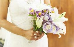 Fiancee in een mooie witte kleding die een mooi die boeket van huwelijksbloemen houden van tedere in hand rozen en lelies worden  royalty-vrije stock foto's