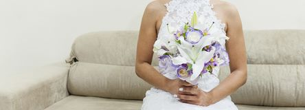 Fiancee in een mooie witte kleding die een mooi die boeket van huwelijksbloemen houden van tedere in hand rozen en lelies worden  stock afbeeldingen