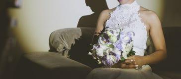 Fiancee in een mooie witte kleding die een mooi die boeket van huwelijksbloemen houden van tedere in hand rozen en lelies worden  stock afbeelding