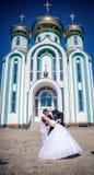 Fiancee and groom, against church Stock Photos