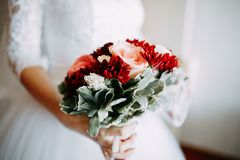 Fiancee holding bouquet of white and red flowers. Fiancee holding bouquet. Hands on the wedding dress. White and red flowers with green leaves royalty free stock photo