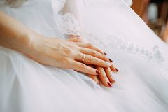 Fiancee hands with ring on the wedding dress. Fiancee holding hands on the white dress. Wedding ring and manicure, bridal veiling stock photography