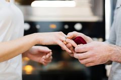 Fiancee. Man putting engagement ring on his fiancee finger stock image