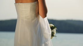 Fiancee in perfect bridal dress stands on berth near water stock video