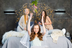 Fiancee throwing bouquet. Happy young fiancee in veil throwing bouquet to her girlfriends on bed royalty free stock photography