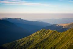 Fianco di una montagna con erba verde fotografie stock