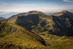 Fianco di una montagna con erba verde, la valle ed i picchi fotografie stock