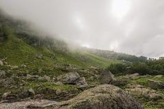 Fianco di una montagna con i cespugli coperti di nuvole Immagini Stock