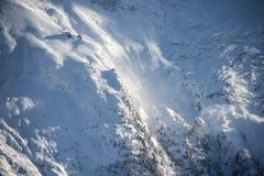 Fianco di una montagna coperto di neve con gli alberi ed il piccolo Ca funicolare Fotografia Stock