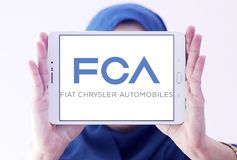 Fiat Chrysler Automobiles, FCA company logo. Logo of Fiat Chrysler Automobiles, FCA company on samsung tablet holded by arab muslim woman. FCA is an Italian royalty free stock photography