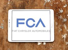 Fiat Chrysler Automobiles, FCA company logo. Logo of Fiat Chrysler Automobiles, FCA company on samsung tablet on wooden background. FCA is an Italian-controlled stock photos