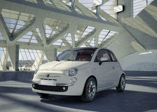 Fiat 500 city car in the middle of building environment. Fiat 500 city white car, alone in the middle of a huge modern building environment Royalty Free Stock Photos