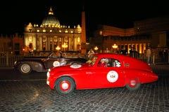 Fiat rojo 508, 1938, y Alfa Romeo marrón 6C 2500, 1940, conduce por la plaza San Pedro el Miglia 1000 Foto de archivo libre de regalías