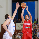 [FIBA Eurochallenge] BC Mures - Szolnoki Olaj. David Vojvoda (right) shoots against Aleksandar Mladenovic (left)  in the first leg of Group H's 2013/2014 FIBA Royalty Free Stock Photos