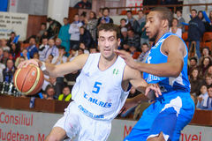 FIBA EuroChallenge :: BC Mures vs Rilski Sportist. Goran Martinic drives against Sean Barnette in the FIBA EuroChallenge game between BC Mures from Romania and stock image
