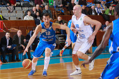 FIBA EuroChallenge :: BC Mures vs Rilski Sportist. Zlatin Georgiev drives the ball against Ivan Ivanovic in the FIBA EuroChallenge game between BC Mures from royalty free stock photo