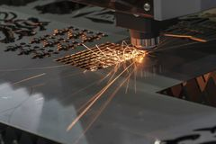The fiber laser cutting machine cutting the sheet metal plate. The sheet metal manufacturing process by laser cutting machine control by CNC program stock photo