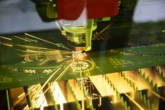The fiber laser cutting machine. Cutting the sheet metal plate with the sparking light.Hi-technology manufacturing concept royalty free stock photos