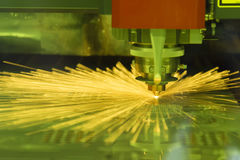 The fiber laser cutting machine. Cutting the sheet metal plate with the sparking light.Hi-technology manufacturing concept stock image