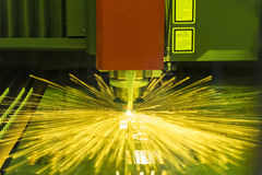 The fiber laser cutting machine. Cutting the sheet metal plate with the sparking light. Hi-technology manufacturing concept royalty free stock images