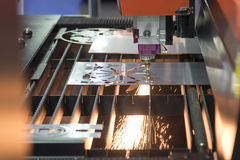The fiber laser cutting machine. Cutting the sheet metal plate with the sparking light.Hi-technology manufacturing concept stock images