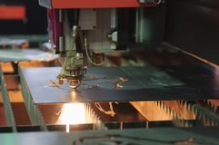 The fiber laser cutting machine. Cutting the sheet metal plate with the sparking light.Hi-technology manufacturing concept royalty free stock photography