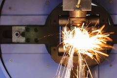 The fiber laser cutting machine. Cutting the steel pipe with the sparking light.The fire flame from Stock Photography