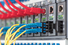 Fiber Optic cables connected to an optic ports. And UTP Network cables connected to an Fast/Giga Ethernet ports stock image