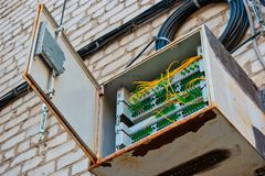 Fiber Optic Switch Panel On Apartment Building Wall With Coil Of Wires Near. Fiber Optic Switch Panel On Apartment Building Wall With Coils Of Wires Hanging Near royalty free stock images