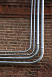 Fiber and power conduits. Fiber and power rigid conduits installed on the brick wall royalty free stock photo